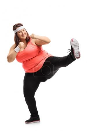 Photo for Full length portrait of an overweight woman kicking isolated on white background - Royalty Free Image