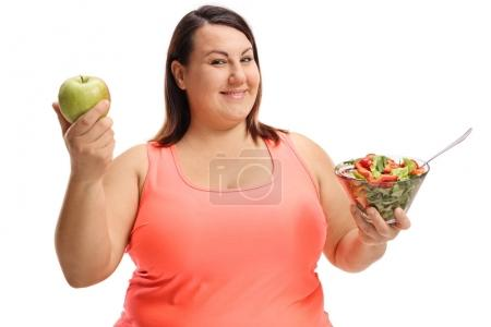 Overweight woman holding an apple and a salad isolated on white background