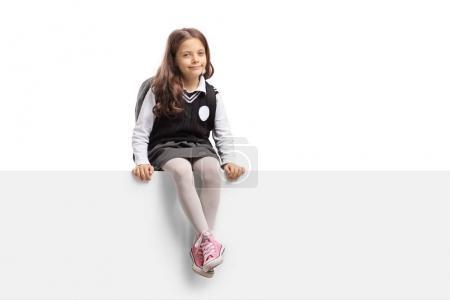 Pequeña colegiala sentada sobre un panel aislado sobre fondo blanco