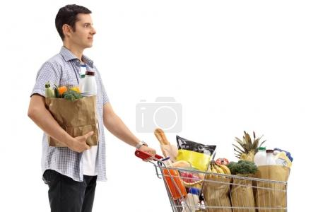Photo for Young man with a shopping bag and a shopping cart filled with groceries isolated on white background - Royalty Free Image