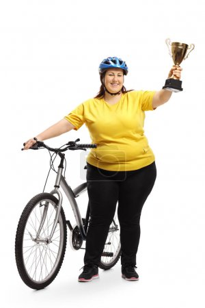 Full length portrait of an overweight woman with a bike and a golden trophy isolated on white background