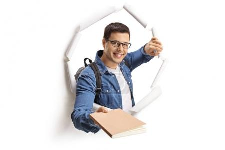 Student giving a book through a paper hole isolated on white background