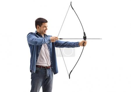 Young man aiming with a bow and arrow isolated on ...