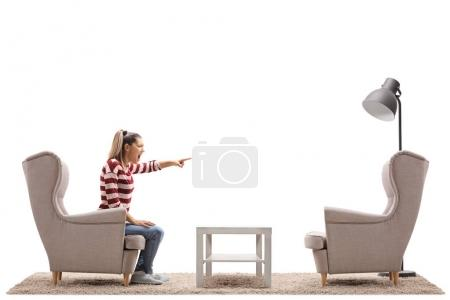 Young woman arguing with an empty armchair isolated on white background