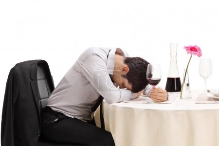Drunk man sitting at a restaurant table with his head down isolated on white background