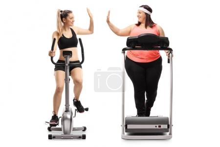 Full length profile shot of two young women exercising and high-fiving each other isolated on white background