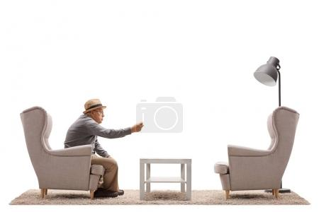 Angry mature man arguing with an empty armchair isolated on white background
