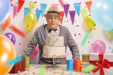 Elderly man blowing candles on a birthday cake with confetti streamers flying around him