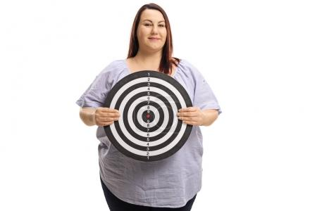 Overweight woman holding a target isolated on white background