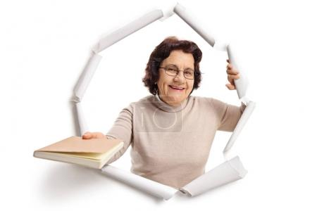 Elderly woman breaking through paper and giving a book