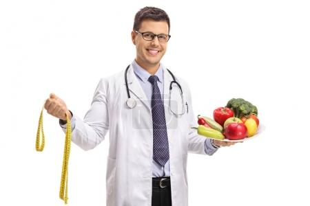 Photo for Doctor with a measuring tape and a plate with vegetables and fruit isolated on white background - Royalty Free Image