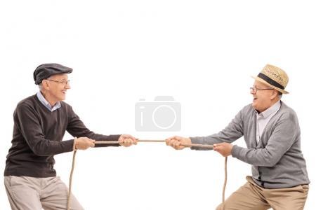 Seniors playing tug of war isolated on white background