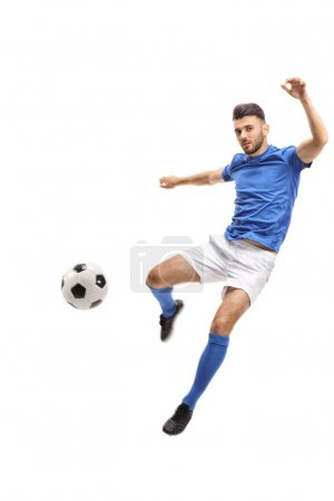 Male soccer player kicking a football in mid-air isolated on white background