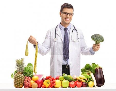 Photo pour Médecin tenant un ruban à mesurer et un brocoli derrière une table avec des fruits et légumes isolés sur fond blanc - image libre de droit