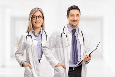 Female doctor and a male doctor with a clipboard looking at the camera and smiling