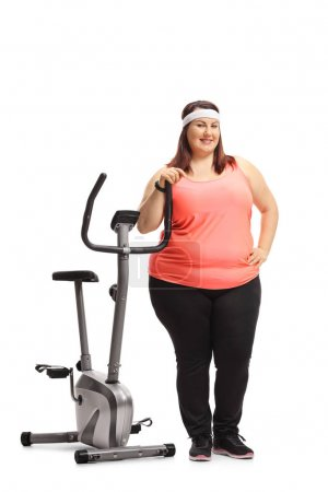 Full length portrait of an overweight woman leaning on a stationary bike isolated on white background
