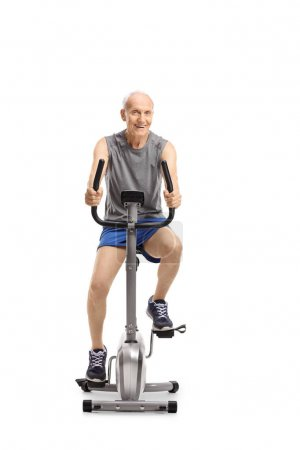 Senior riding an exercise bike and looking at the camera isolated on white background