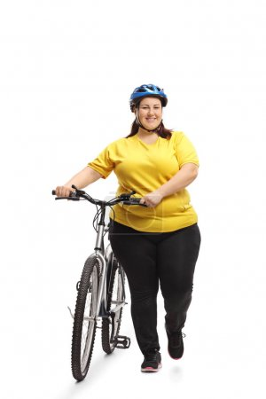 Full length portrait of an overweight woman with a bicycle walking towards the camera isolated on white background