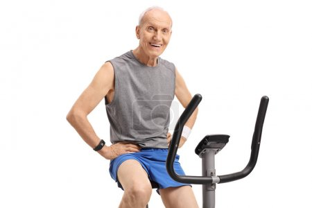 Senior on an exercise bike looking at the camera and smiling isolated on white background
