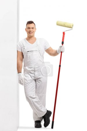 Full length portrait of a painter with a paint roller leaning against a wall isolated on white background