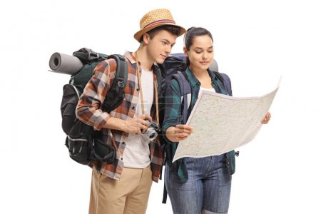 Teenage tourists looking at a map isolated on white background