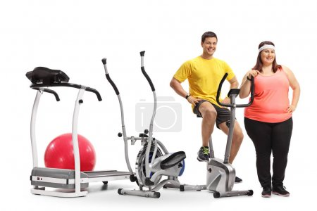 Photo for Young man and an overweight woman with exercise machines isolated on white background - Royalty Free Image