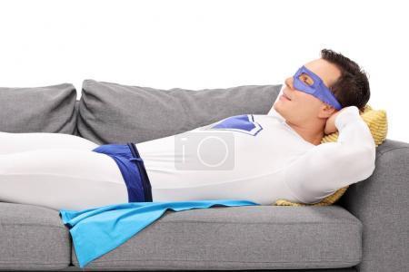 Photo pour Homme en costume de super héros dormant sur un canapé isolé sur fond blanc - image libre de droit