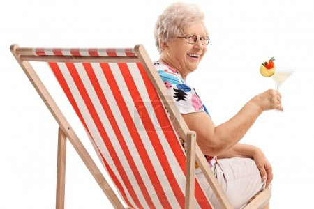 Photo for Mature woman seated in a deck chair holding a cocktail isolated on white background - Royalty Free Image