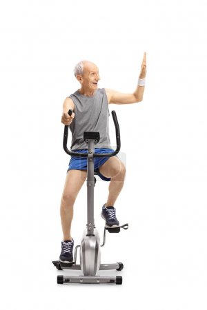 Photo for Senior exercising on a stationary bike making a high-five gesture isolated on white background - Royalty Free Image