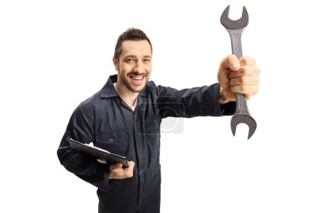 Photo pour Mécanicien automobile tenant une clé et un presse-papiers et souriant à la caméra isolée sur fond blanc - image libre de droit