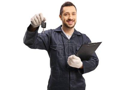 Photo pour Mécanicien automobile avec une clé de voiture et un clibboard isolé sur fond blanc - image libre de droit