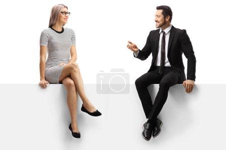 Photo pour Une femme occasionnelle et un homme d'affaires assis sur un panneau et parlant seuls sur fond blanc - image libre de droit