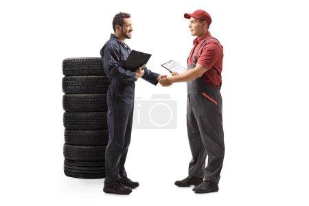 Photo pour Plan de profil complet d'un mécanicien automobile serrant la main d'un livreur isolé sur fond blanc - image libre de droit