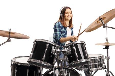 Photo pour Adolescente avec écouteurs jouant du tambour isolée sur fond blanc - image libre de droit
