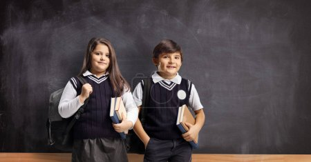 Photo for Children in school uniforms with books standing in front of a school blackboard - Royalty Free Image