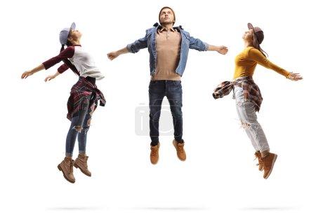 Photo pour Plan complet du profil de deux jeunes femmes et d'un mec effectuant un saut de danse isolé sur fond blanc - image libre de droit