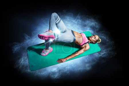 Photo for Professional fitness woman working out and stretching on the black background - Royalty Free Image