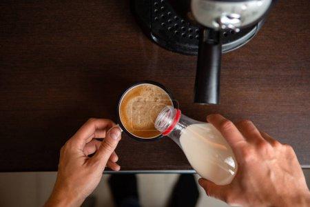 Photo pour Photo d'une cafetière, mains d'un homme versant du lait dans une tasse de café dans la cuisine - image libre de droit
