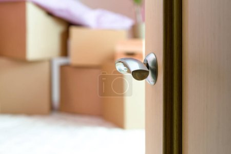 Photo of cardboard boxes, open door in new apartment. Blurred background