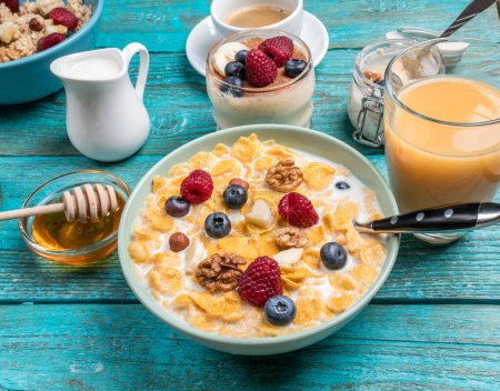 Photo for Bowl with oat flakes with raspberries and blueberries on a blue wooden table. Hot and healthy breakfast and diet food. - Royalty Free Image