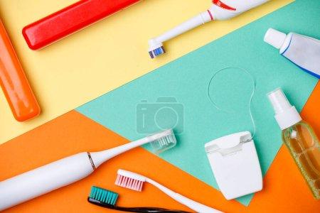 Photo pour Image de brosses à dents, tubes de pâtes, fil dentaire sur fond orange, vert et jaune - image libre de droit