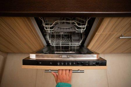 Photo pour Photo de la main d'un homme ouvrant un lave-vaisselle dans un appartement - image libre de droit