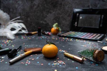 Photo pour Image de Noël décoration, mandarine, brosses, rouge à lèvres, palette avec ombres sur table noire avec espace pour le texte - image libre de droit