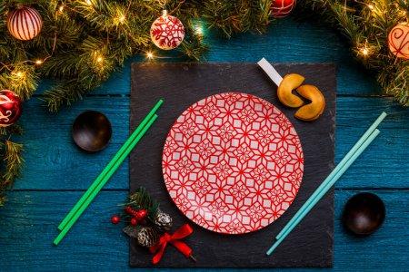 Photo pour Photo du Nouvel An branches de sapin, tableau noir, bâtonnets de sushi, biscuits de prédiction, assiettes à motif rouge sur fond de bois bleu - image libre de droit