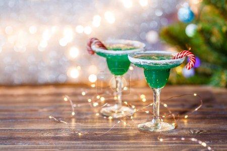 Photo pour Image de Noël de deux verres à vin avec cocktail vert, bâtonnets de caramel et guirlande sur fond bleu flou - image libre de droit