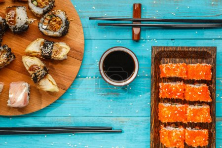 Photo for Rolls on round wooden board and plate on blue table - Royalty Free Image