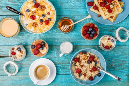 Photo for Breakfast table with waffles, oatmeal, cereals, coffee, juice and fresh berries. Healthy breakfast - Royalty Free Image