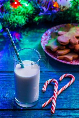 Photo pour Image de table bleue avec biscuits de Noël, verre de lait, bâtonnets de caramel, branches d'épinette avec guirlande en feu - image libre de droit