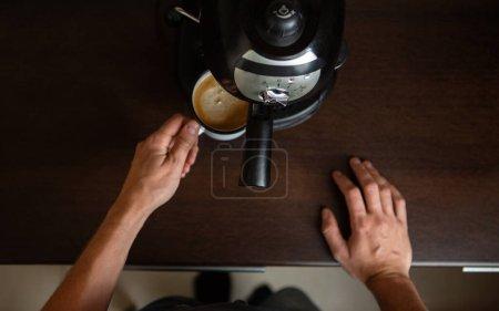 Photo pour Photo d'une cafetière, mains d'un homme versant du café dans une tasse dans la cuisine - image libre de droit