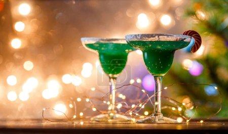 Photo pour Photo de Noël de deux verres à vin avec cocktail vert et guirlande sur fond bleu flou. - image libre de droit